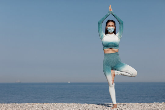 young woman in mask practicing yoga outdoor