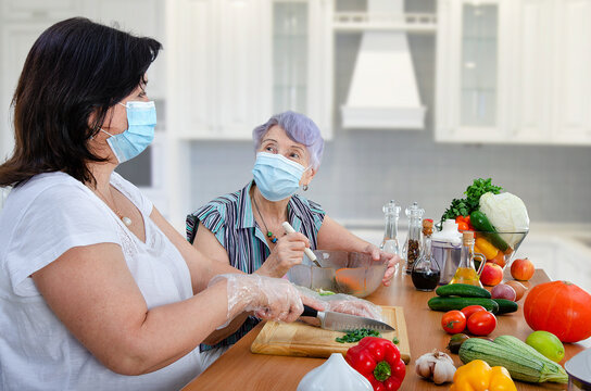 Despite the coronavirus pandemic, a caregiver and a senior adult woman cook together a vegetable salad once a week in the kitchen. Both put on protective masks.