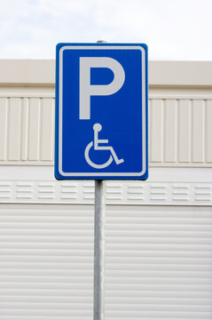 Blue disabled parking sign with a building in the background in Arnhem, Netherlands