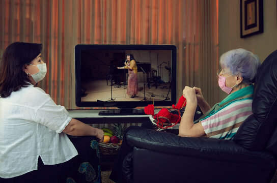 An elderly woman knits and watches a retro music channel on TV. A caregiver sits nearby.  The carer in a white shirt looks at the lady. Both are wearing protective masks due to the pandemic.