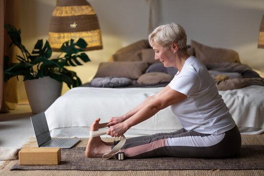 Senior caucasian woman practicing yoga, sitting in Seated forward bend exercise, paschimottanasana pose