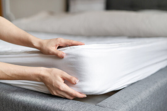 Woman putting new orthopedic mattress on sleeping bed