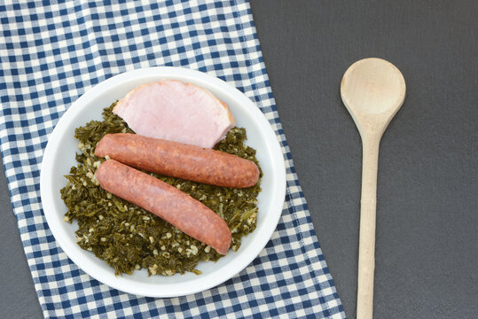 Fresh cooked kale with sausages, meat and wooden spoon  in the pan on black background