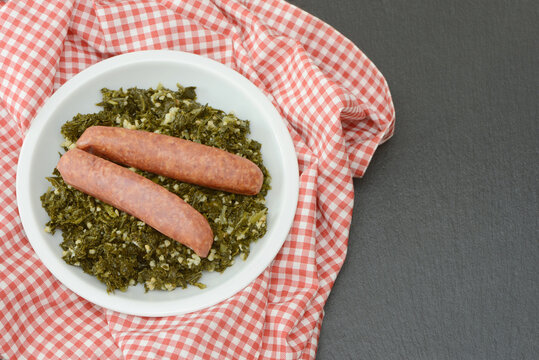 Fresh cooked kale with sausages in the pan on black background