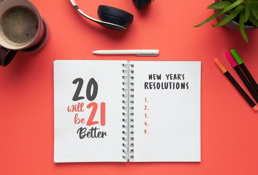 Stock photo of 2021 new year notebook with list of resolutions and objects on a red background