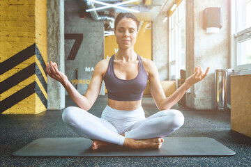 Young beautiful fitness woman in sportswear sitting on yoga mat in lotus pose at gym and meditation, keeping eyes closed