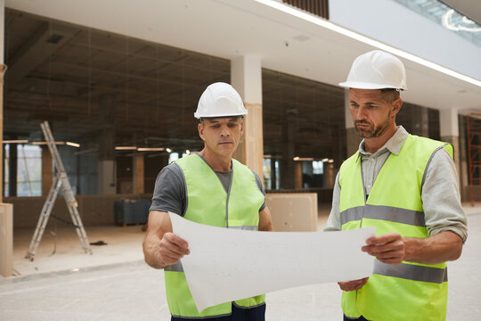 Waist up portrait of two professional building contractors looking at plans while standing at construction site, copy space
