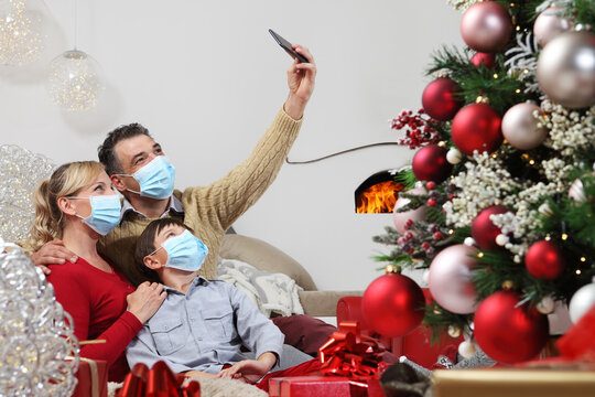 Merry christmas, happy family wear surgical mask, forced to stay at home alone because of the coronavirus, communicates with mobile phone remotely, christmas lockdown concept
