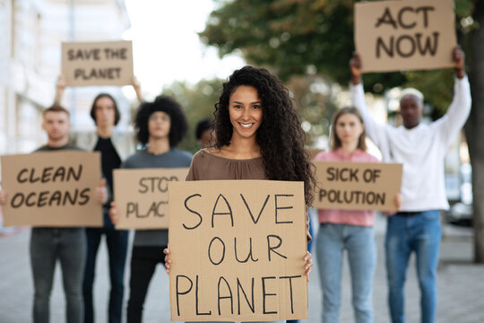 Cheerful lady with SAVE OUR PLANET placard