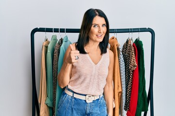 Obraz Middle age brunette woman working as professional personal shopper doing happy thumbs up gesture with hand. approving expression looking at the camera showing success. - fototapety do salonu