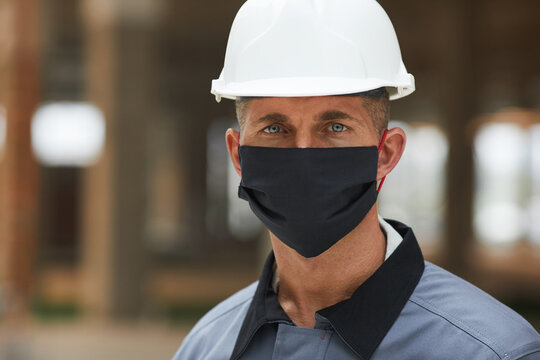 Head and shoulders portrait of mature worker wearing mask and looking at camera while working on industrial site, copy space