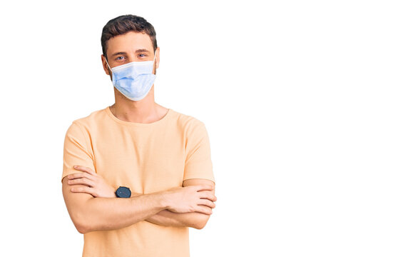 Handsome young man with bear wearing medical mask for coronavirus happy face smiling with crossed arms looking at the camera. positive person.