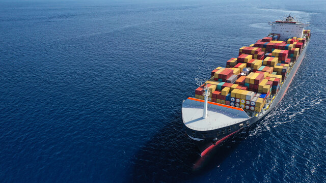 Aerial drone photo of huge container tanker ship carrying truck size colourful containers in deep blue open ocean sea