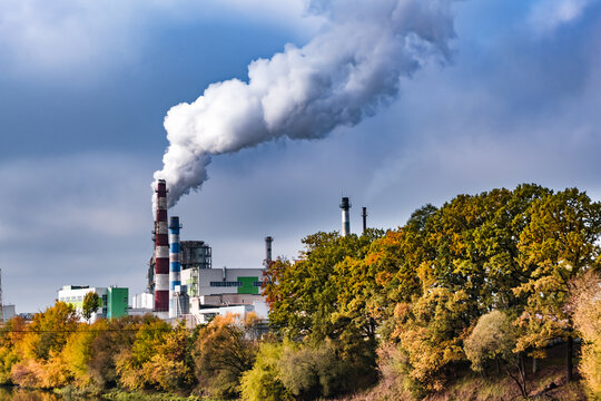 pipes of woodworking enterprise plant sawmill near river with autumn red yellow trees. Air pollution concept. Industrial landscape environmental pollution waste of thermal power plant
