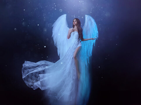 Fantasy woman angel soars in the air with white huge bird wings. Ghost girl in levitation flies. Dark night background, magical light. Lady goddess in white dress, fabric waving fluttering in motion.