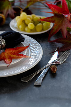 A closeup to autumn style dinner serving with white plates black napkins and red autumn leaves