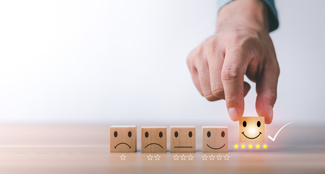 best excellent business services rating customer experience. Satisfaction survey concept. Hand of a businessman chooses a smiley face on wood block cube. 5 Star Satisfaction.