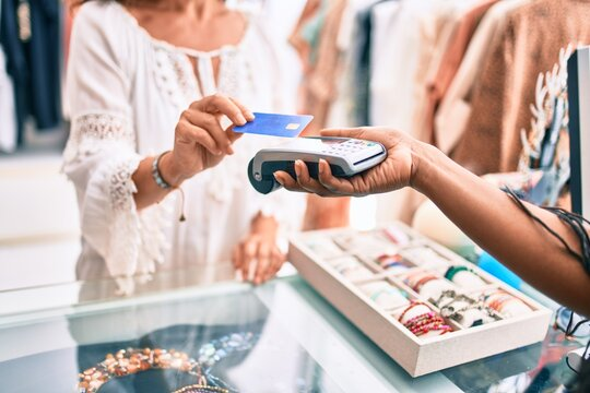 Woman paying purchase using credit card and dataphone at clothing store.