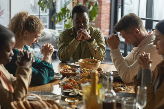 Portrait of African-American man praying with eyes closed while sitting at dinner table during Thanksgiving celebration with friends and family, copy space