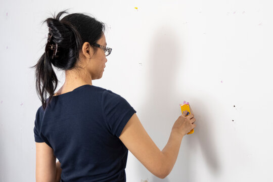 A Filipino woman is patching drywall holes in a wall with pink putty.