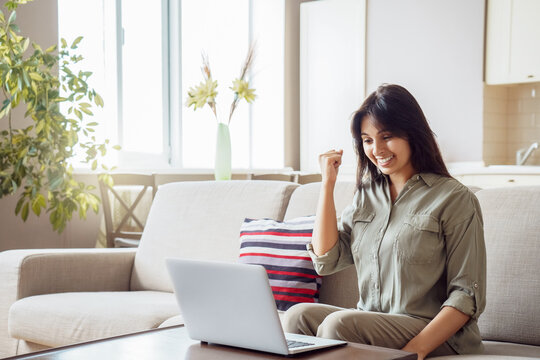 Happy indian woman student, winner celebrating achievement, online bid win, victory, success raising hand in yes gesture looking at laptop feeling glad receiving discount voucher on email at home.