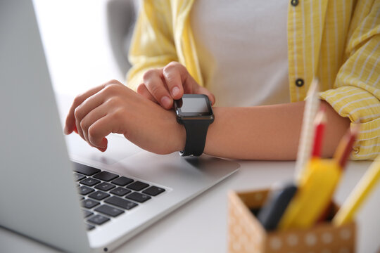 Woman with laptop using smartwatch at white table, closeup