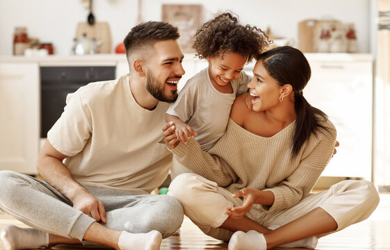 happy multiethnic family mom, dad and child  laughing, playing and tickles    on floor in cozy kitchen at home.