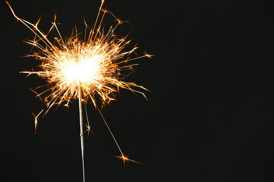 Bright burning sparkler on black background, closeup. Space for text