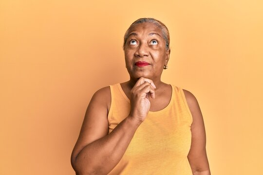 Senior african american woman wearing casual style with sleeveless shirt thinking concentrated about doubt with finger on chin and looking up wondering