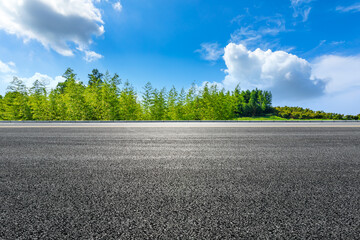 Asphalt road and green bamboo with mountain natural scenery in Hangzhou on a sunny day.