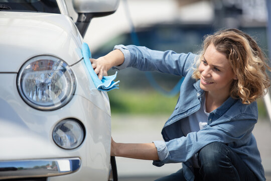 portrait of smiling woman taking care of her car