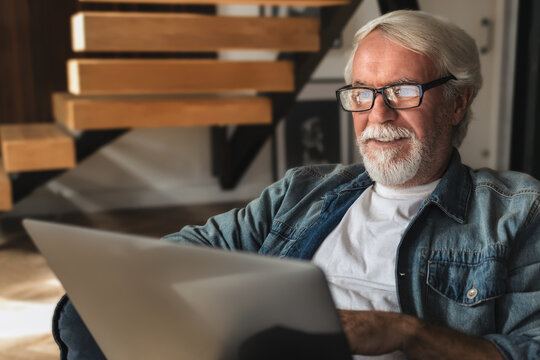 Elderly man with glasses with gray hair and a beard sits at home on the sofa and works or browses social networks on  laptop