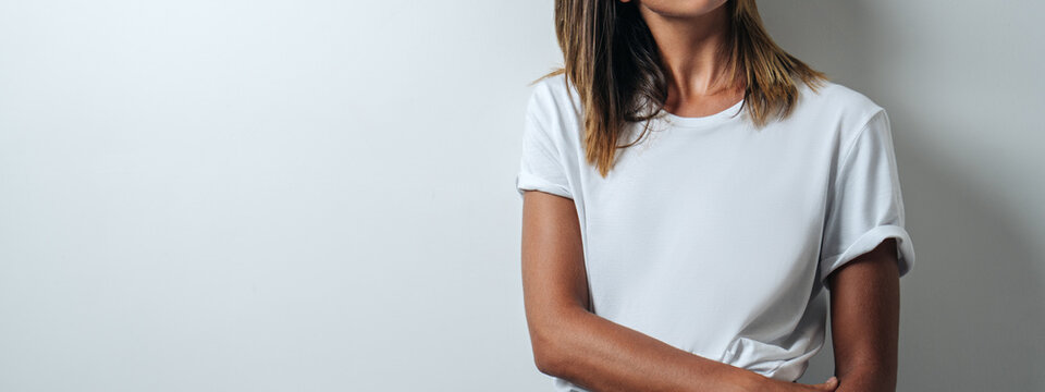 Young and pretty woman in white blank t-shirt wearing glasses, empty wall, horizontal studio portrait. Wide screen, panoramic