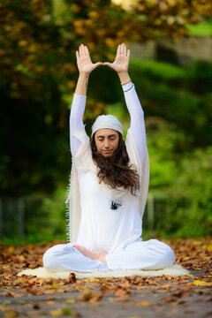 In the autumn park a young woman practices yoga alone