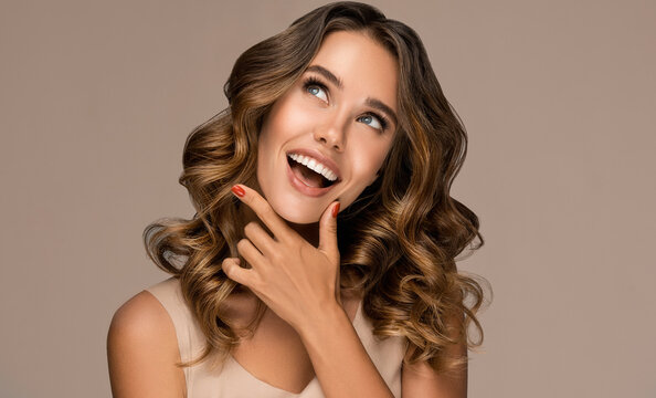 Beautiful smiling woman holding hands near face and  looking to the side  . Beauty girl  with curly hair   . Presenting your product. Expressive facial expressions
