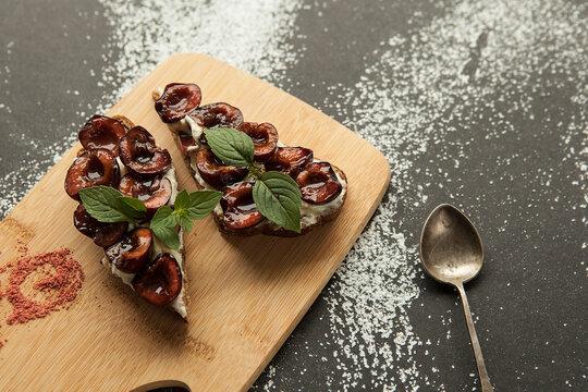 Dessert bruschetta made of rye bread in Italian style, sweet ripe plum and cream cheese, delicious snack