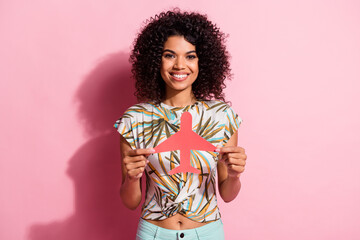 Photo sur Plexiglas Dinosaurs Portrait photo of pretty black skinned curly woman showing paper plane figure smiling isolated on pastel pink color background