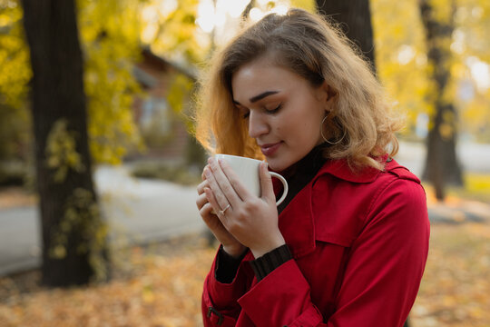 Woman sniff aroma of coffee at the fall day in park