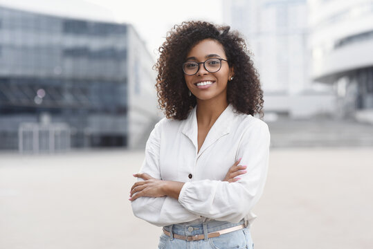 Young businesswoman in a city looking at camera, African-american student girl portrait, Young woman with crossed arms smiling, People, enjoy life, student lifestyle, city life, business concept