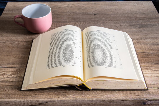An open book with a cup next to it