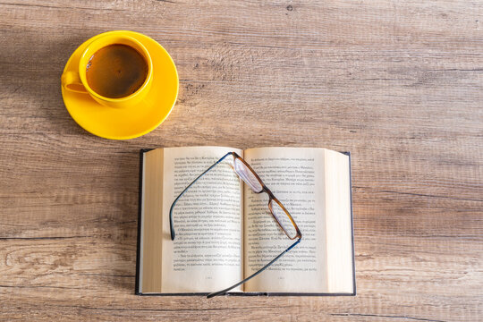 An open book with glasses and a yelloow cup of coffee