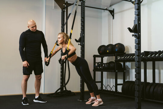 Private workout. Young woman doing push-ups CrossFit suspension training with her personal trainer or coach in a fitness club. The concept of weight loss and gaining muscle mass.