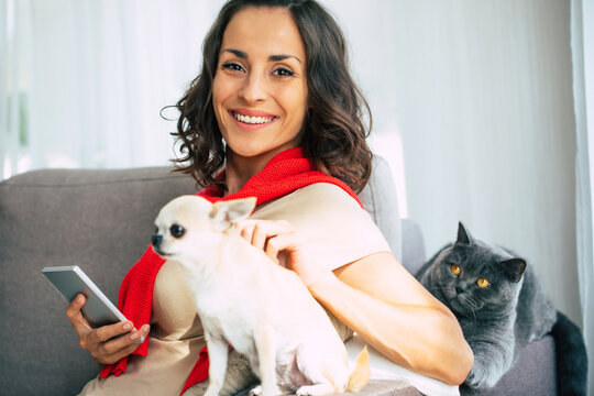 Smiling young gorgeous woman is resting with her pets at home on the couch