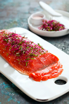 Gravlax, homemade salted sockeye salmon fillet with beetroot sprouts selective focus