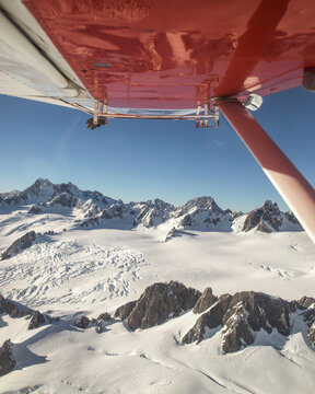 Aerial view from airplane window of snowy mountain peaks and glaciers wing in ice cold winter in Mount Cook National Park, South Island, New Zealand.