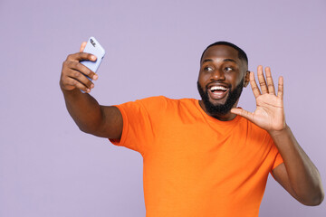 Funny cheerful young african american man 20s in basic casual orange t-shirt doing selfie shot on mobile phone waving greeting with hand isolated on pastel violet colour background, studio portrait.