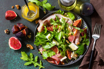 Healthy food concept. Autumn salad with figs, prosciutto, arugula, spinach, cheese, walnuts and honey on a stone countertop. Top view flat lay background.