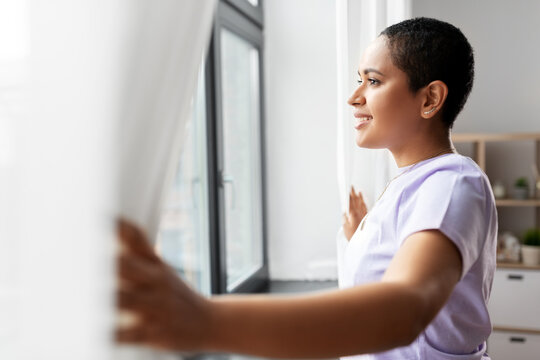 people and leisure concept - happy young african american woman looking out of window at home