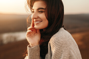 Happy young woman enjoying sunset in nature