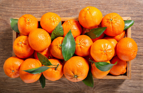 Fresh mandarin oranges fruit or tangerines with leaves in a wooden box